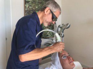 Photo illustrant le Dr.Perrenoud utilisant le laser Genesis sur une cliente.