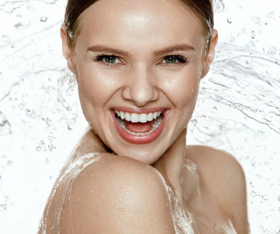 Image montrant une femme souriante et de l'eau pour illustrer l'hydratation.