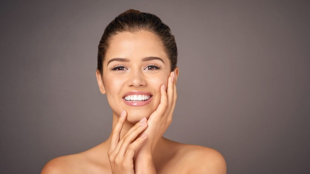 Photo montrant une femme se touchant le visage pour illustrer l'article à propos du traitement skinbooster